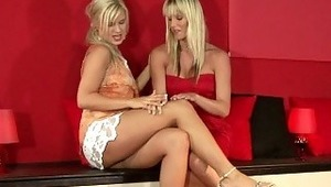 Briget and Geena - Elegantly dressed blondes Briget and Geena, in red, share a glass of juice then a passionate tongue kiss before they strip off their dresses. They take turns fingering and licking each other's pink pussies on a mantle, then a bean-