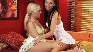 Carie and Katy - Raven haired Carie and blonde Katy kiss passionately in an art deco living room, then eagerly strip off their dresses and suck one another's firm tits and taut nipples. They slip off their panties, spread their legs on a sofa and tak
